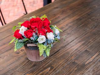 Fototapeta rose artificial flowers in the pot , on the wood desk, in the ga obraz