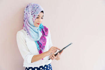 Muslim woman standing , holding and touch tablet computer
