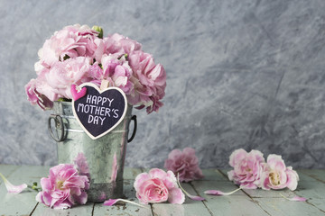 Pink carnation flowers in zinc bucket with happy mothers day let