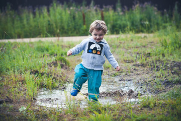 Cute curly baby dressed in boots and rubber pants jumping in a puddle. Funny kid with children's happiness.
