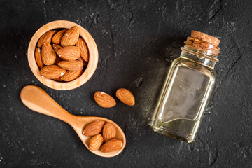 cosmetic almond oil in glass bottle on dark background