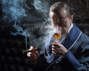 Man in an elegant robe smoking a cigar and drinking alcohol