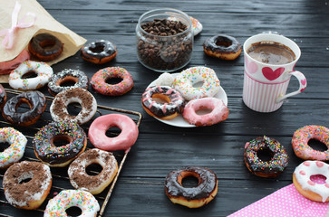 Morning breakfast. Lots of donuts and coffee on the white wooden background