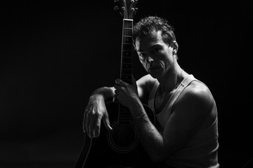 Low key portrait of man with his guitar. Dark background