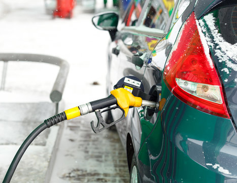 Car refueling on a petrol station in winter close up