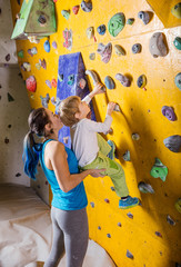 Аemale bouldering instructor helping boy climb artificial wall