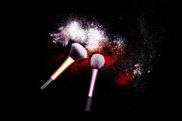 Makeup brushes with powder spilled glitter dust on black background. Red powder on black table.