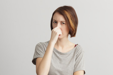 Girl closes her nose because of the odor and stench.