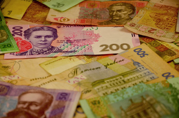 Many Ukrainian money bills of various denominations and colors. Ukrainian banknotes with portraits of historical and cultural figures and historical institutions. Modern Ukrainian money - hryvnia. UAH