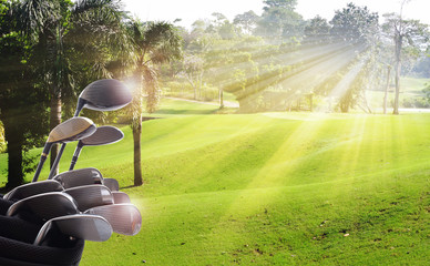 Golf clubs drivers over beautiful green course at the sunset, sunrise time.