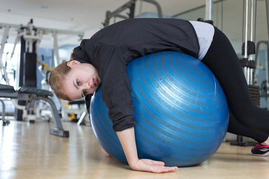 Blonde girl or young woman with green eyes and red lips lying on blue gymnastic ball looking exhausted, tired, bored and weary wearing black jacket, grey t-shirt with training apparatus on background