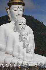 sitting white buddha statue well alignment in front of mountain in thailand
