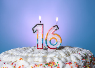 Tasty cake with candles for sixteenth birthday on blue background