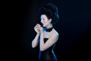 portrait of the actress brunette woman with high hair, a black collar with roses on a neck and in a corset in old style on a black background