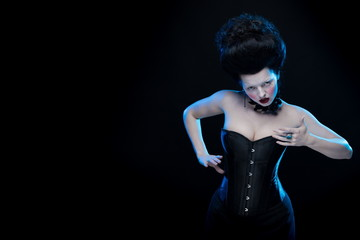 portrait of the actress brunette woman with high hair, black chokers with roses on a neck and in a corset in old style on a black background