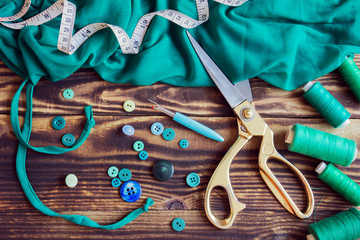 sewing tools, green fabric, threads and buttons on a wooden background