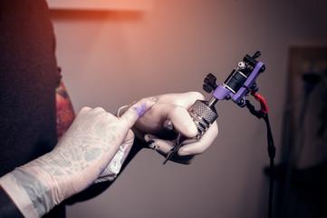 Professional tattooist with tattoo machine in hand
