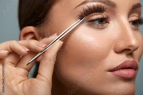 c281cd74421 Beauty Makeup. Woman Applying Black False Eyelashes With Tweezer ...