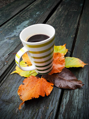 Cup of coffee. Underneath the autumn leaves