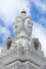 White statue of buddha image with blue sky and cloud