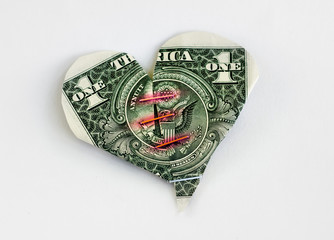 Heart laid out from banknotes one dollar, and sealed with paper clips.