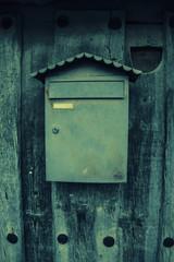 Viejo buzón de metal en una puerta de madera