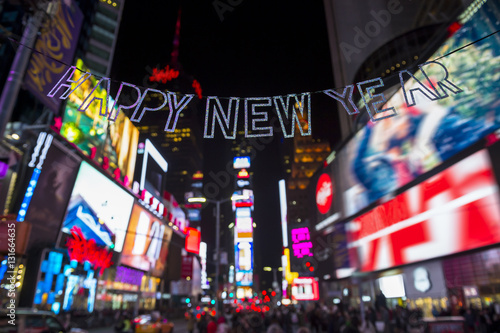 glittery happy new year message strung across the flashing lights of times square new york