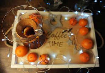 "Mandarins, coffee, decoration and garland on a wooden tray with engraved ""coffee time"". Holiday atmosphere, holiday, Christmas."