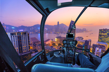 Helicopter cockpit flying aerial view of Victoria Harbor, skyscrapers and Hong Kong skyline at night.