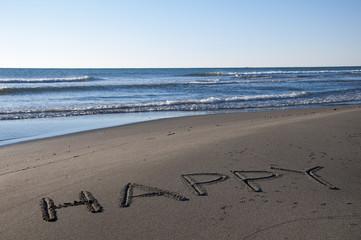 Word happy handwritten on sand