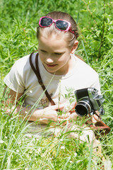 Girl child photographing old camera.