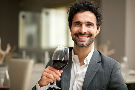 Man tasting a glass of red wine in a restaurant