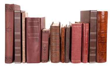 Varying ages and designs of the spines of old books on a shelf, isolated