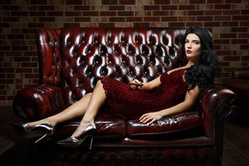 beautiful girl lying on the sofa. red dress. curly black hair