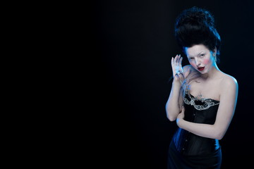 actress brunette woman with high hair in corset decorated with feathers in antique style on a black background