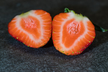 Single sliced strawberry on gray stone