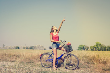 Beautiful pinup girl having fun cycling in fields under bright blue summer sky and pointing up on outdoors copy space background