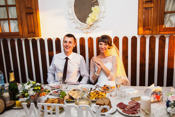 Groom and bride in a white dress in the restaurant. Wedding photography. Happy family