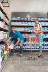 Smiling Couple Buying Dairy Products In Supermarket