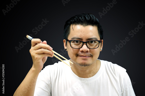 """Asian man holding chopsticks ready to eat on a black ..."
