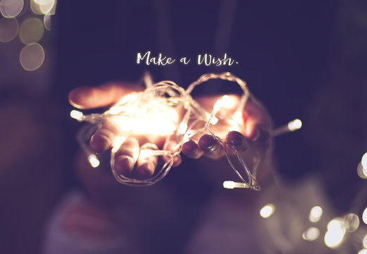 Make a wish word over hand with light bokeh in vintage filter,Ho
