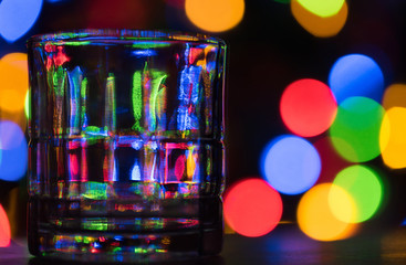 Tumbler glass on dark, multi-colored bokeh background