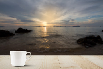 Hot coffee cup with steam on wooden table top on blurred golden sky, sea and island background during sunrise