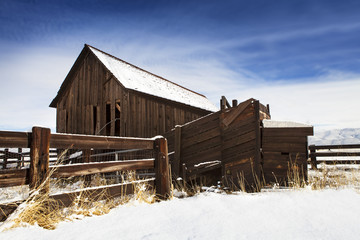 Old barn with fence in winter with snow.