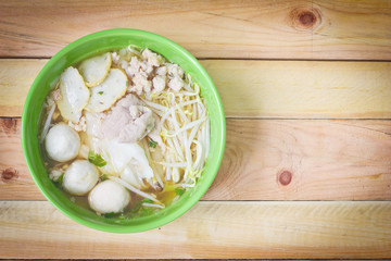 Noodles in green bowl on wood background.