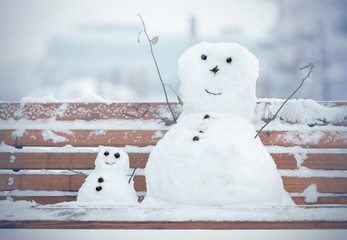 Two Snowman, one big and one small sitting on a bench in the park