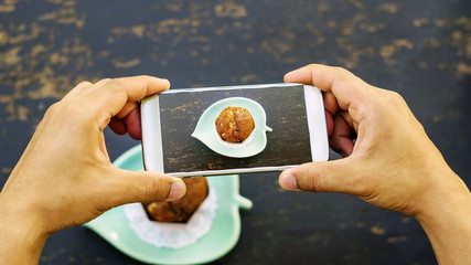 Men take a photo of muffin cake.