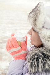 Young woman is drinking coffee on the street while walking on cold winter day. Hands with white take take-out coffee paper cup. Coloring and processing photo with soft focus in instagram style.