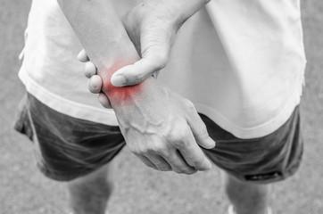 Wrist pain. Male holding hand to spot of wrist pain.