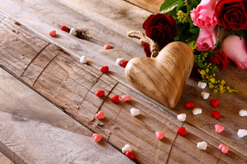red heart and roses on wooden table